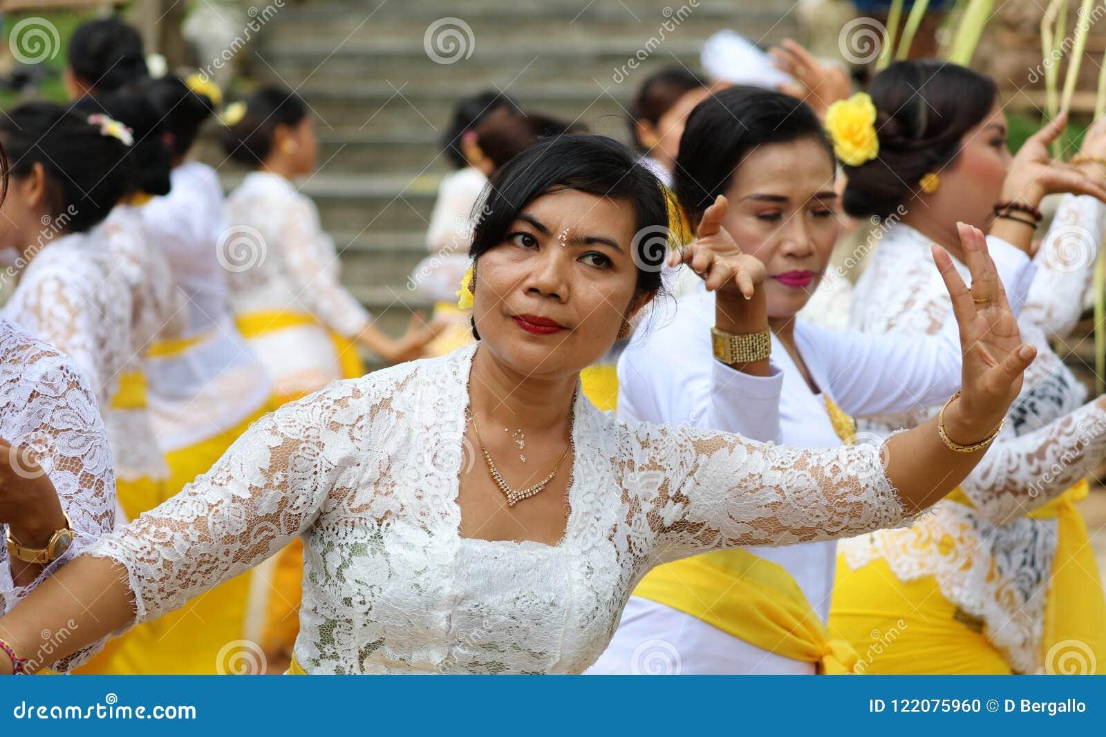 Celebrazione indù a Bali Indonesia, cerimonia religiosa con i colori gialli e bianchi, dancing della donna