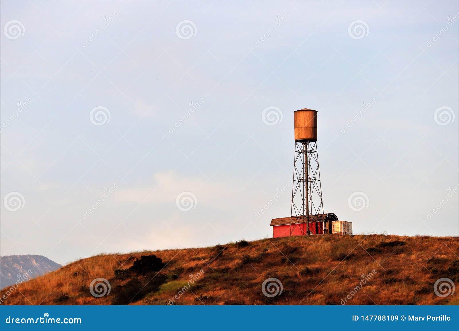 Celeiro vermelho com torre de água em um monte em Califórnia rural