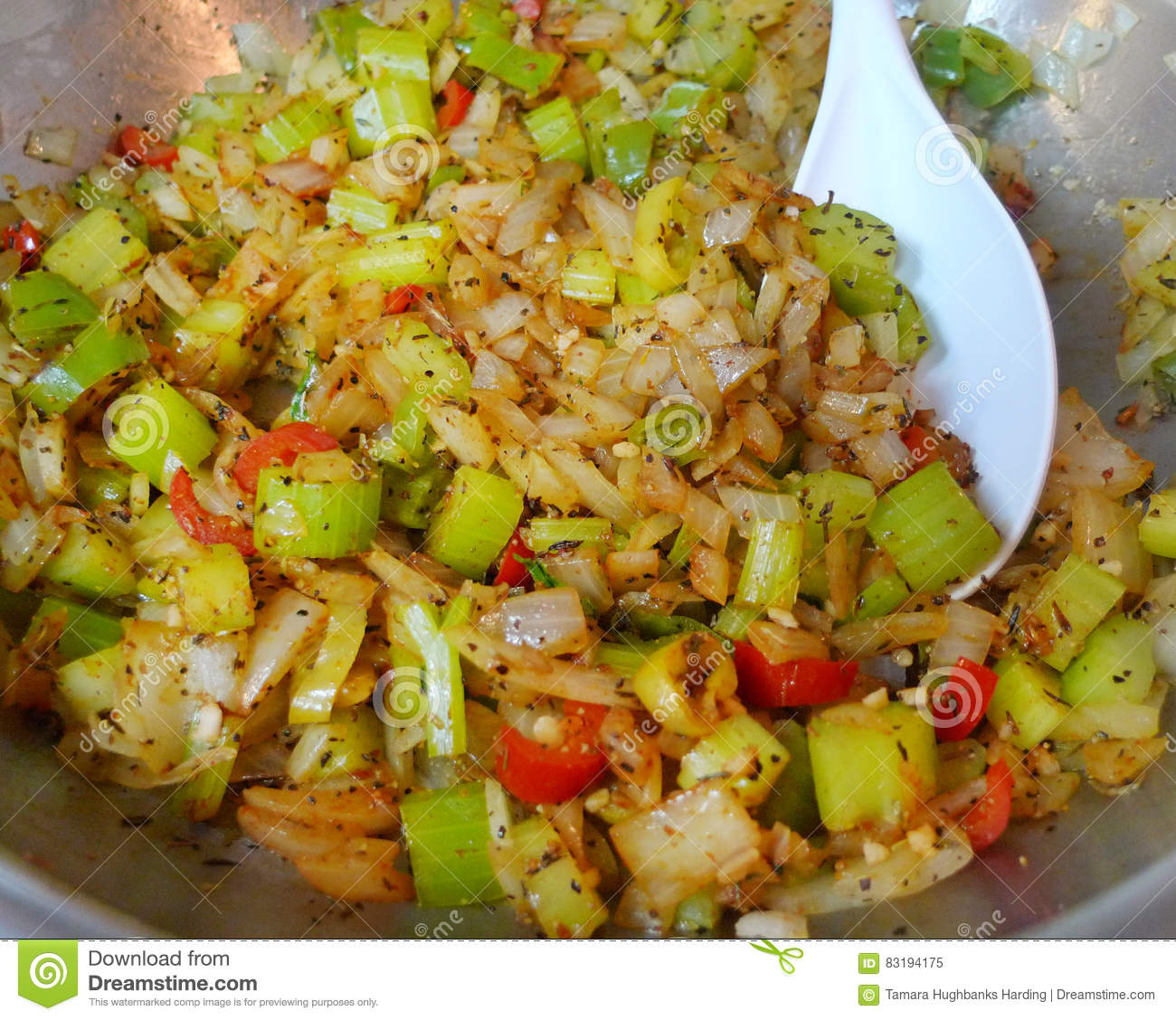 Celery, onions, peppers and spices in pan with spoon