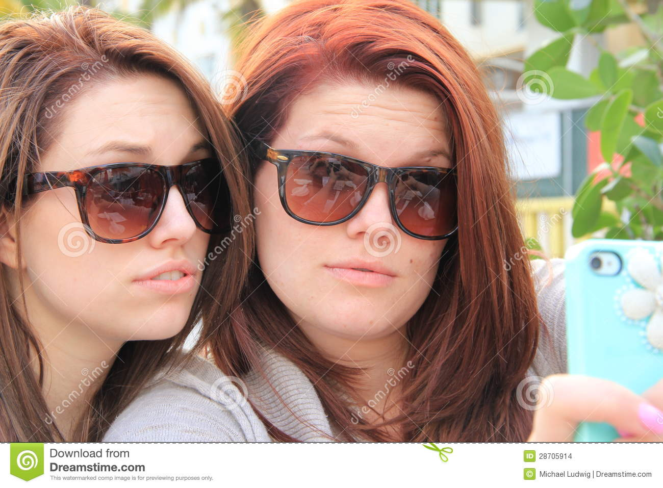 Two ladies using their cell phone for a self Portrait of them selves