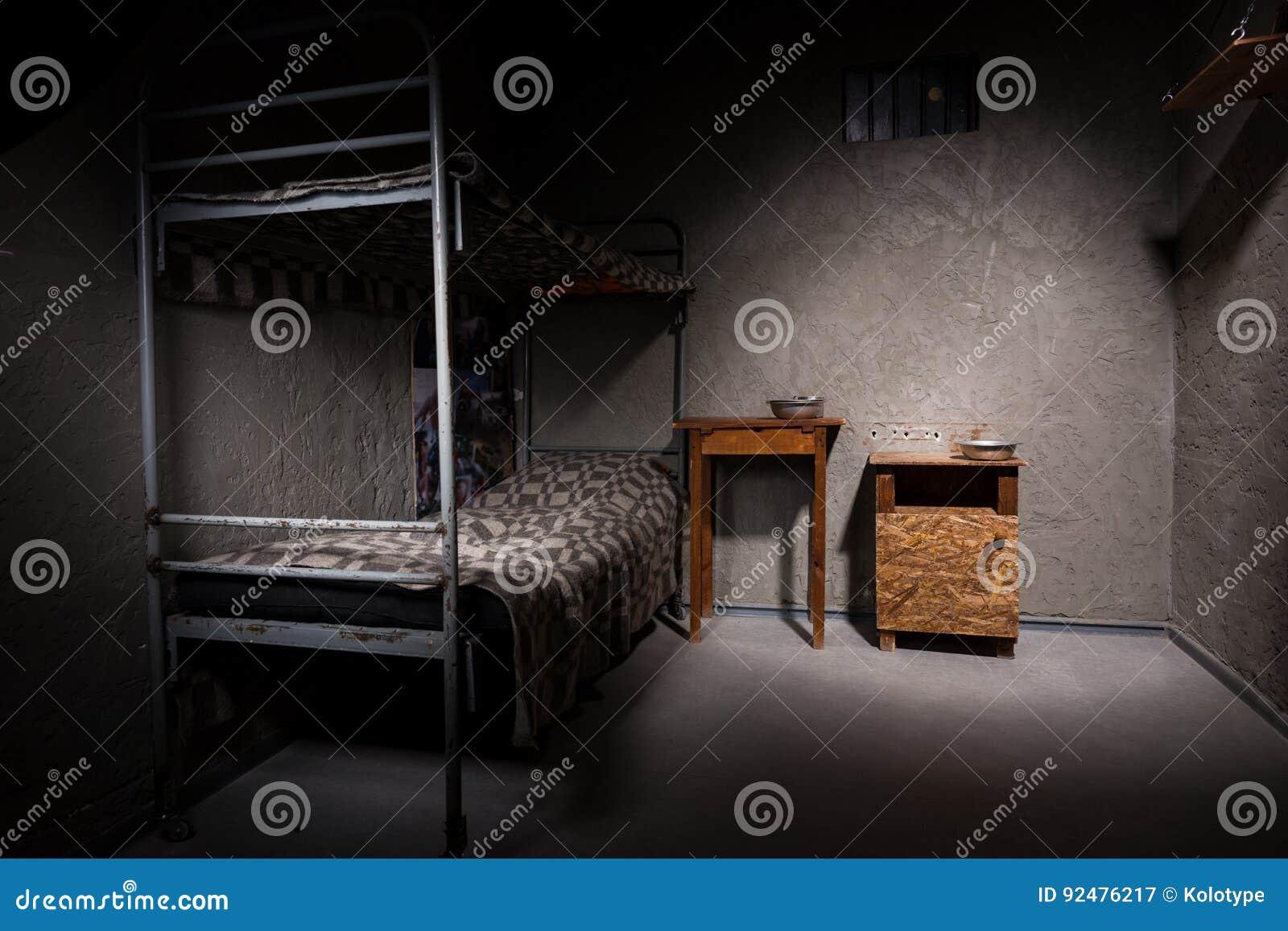 Cellule De Prison Avec Le Lit Superpose De Fer Et La Table De Chevet