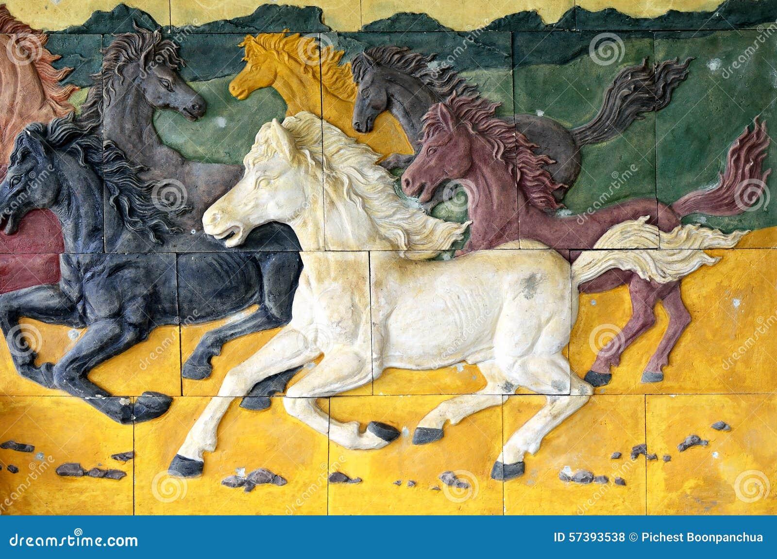 Cement met beeldhouwwerk van paard op de muur