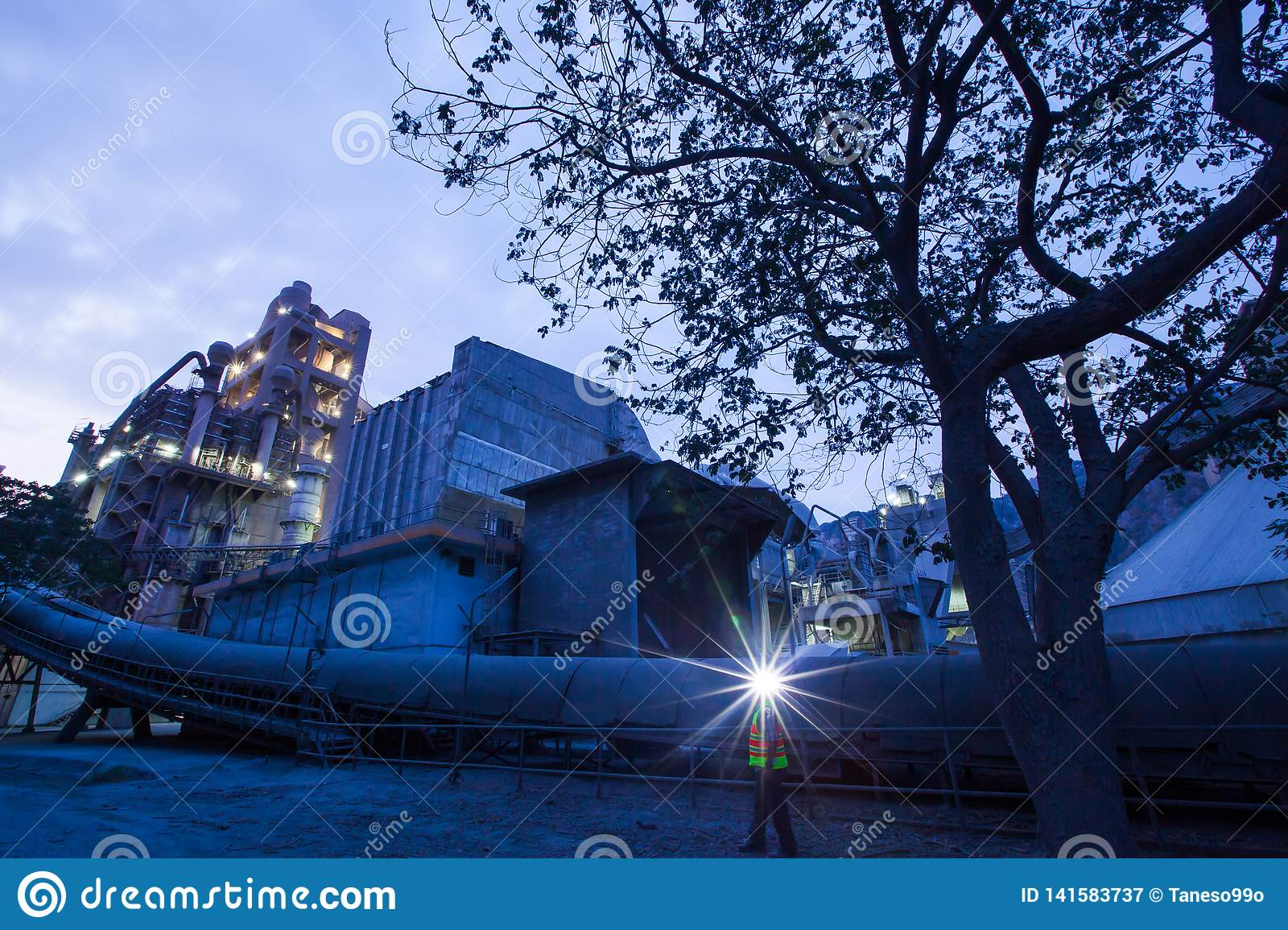 Cement plant factory manufacturing at dusk, sparks of worker with headlamp flashlight during working overtime