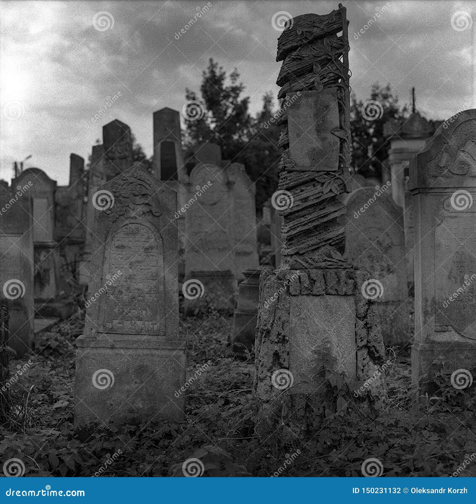 Cementerio judío abandonado viejo con los sepulcros de piedra entre los árboles