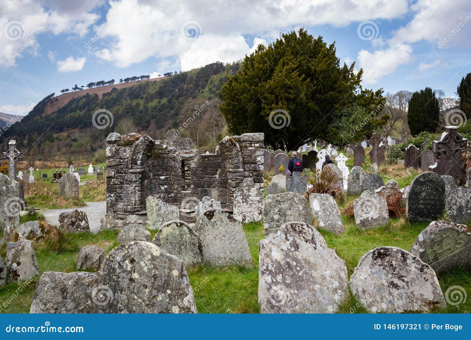 Cemitério antigo velho com lápides e o monte gastos da montanha com céu nebuloso