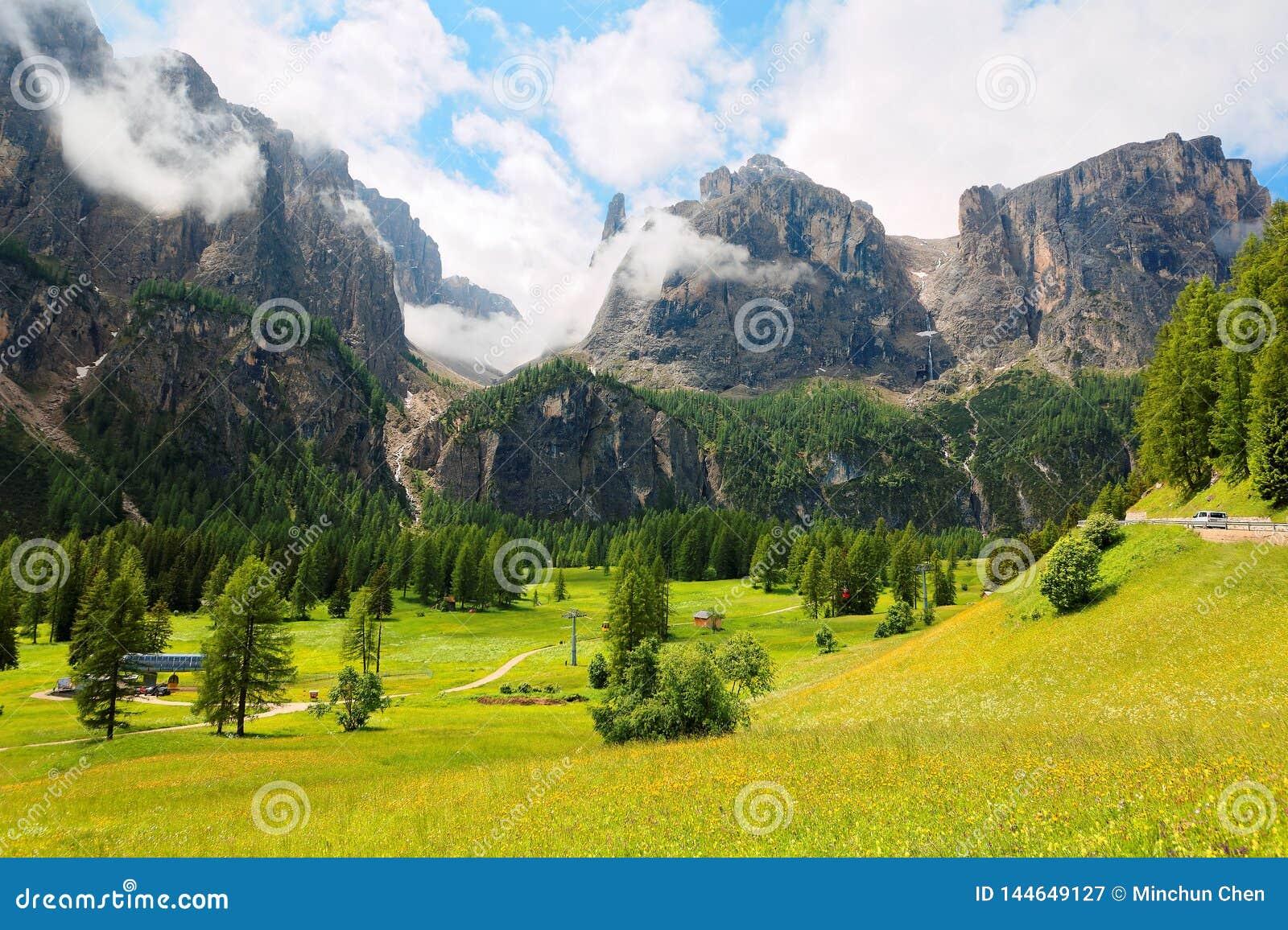 Cenário do verão de montanhas majestosas de Sella com as cachoeiras que caem abaixo dos penhascos rochosos em um vale gramíneo ve