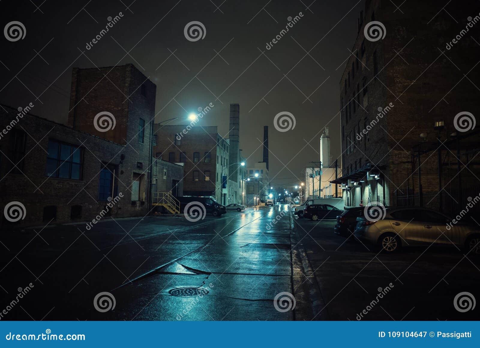 Cenário urbano industrial nevoento da noite da cidade da rua