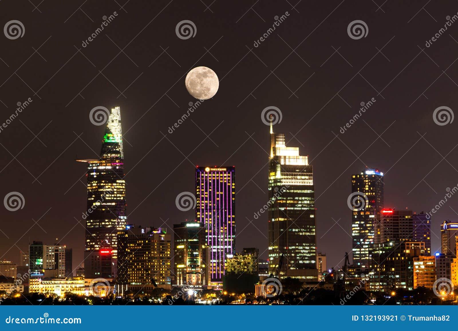 Cena da cidade com a lua que aumenta acima do distrito financeiro central de Ho Chi Minh City na noite