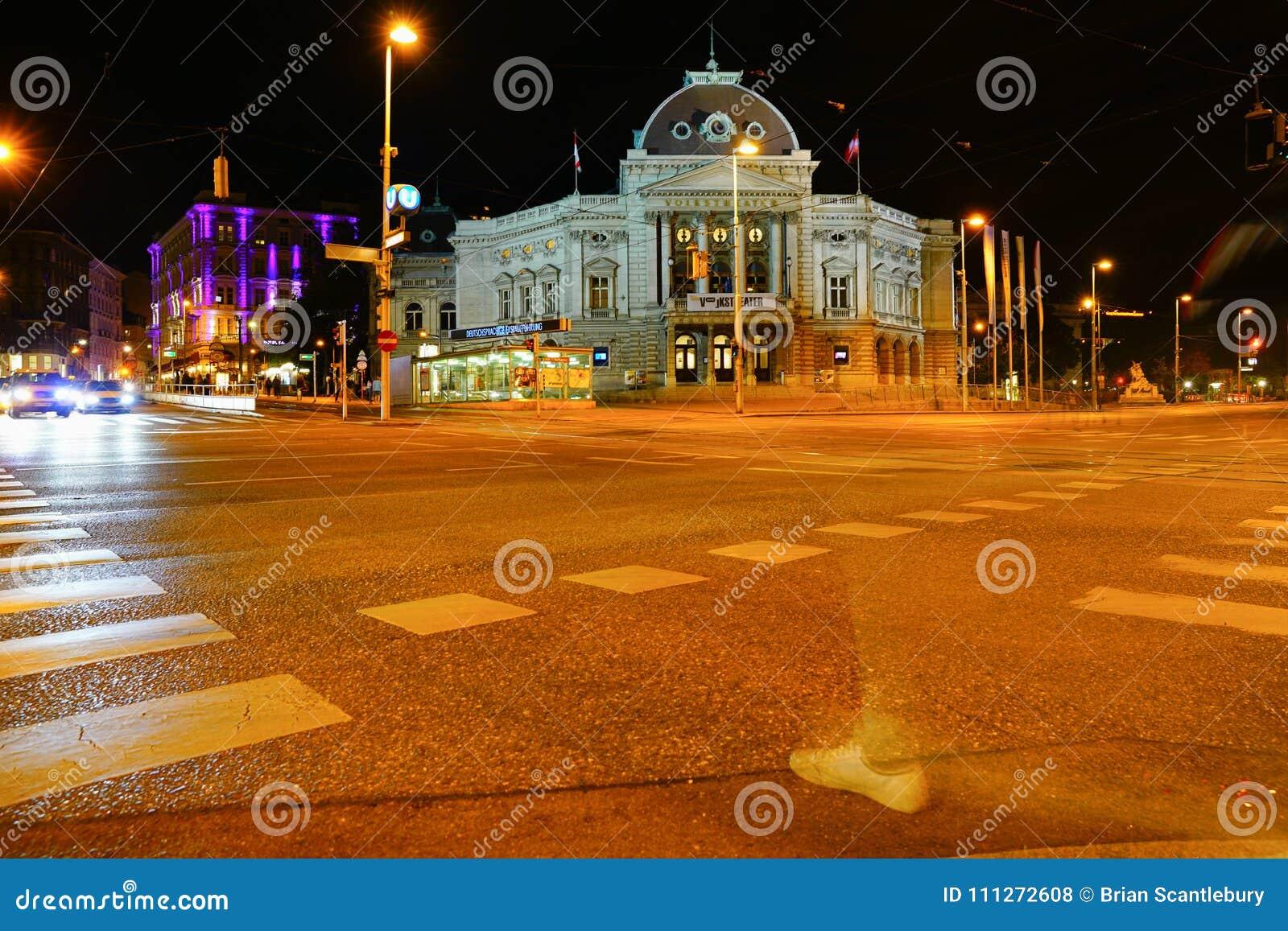 Cena da rua da noite com teatro famoso através da interseção
