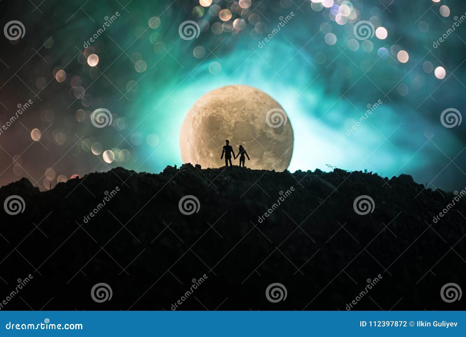 Cena de amor surpreendente Silhuetas dos pares românticos novos que estão sob a luz de lua