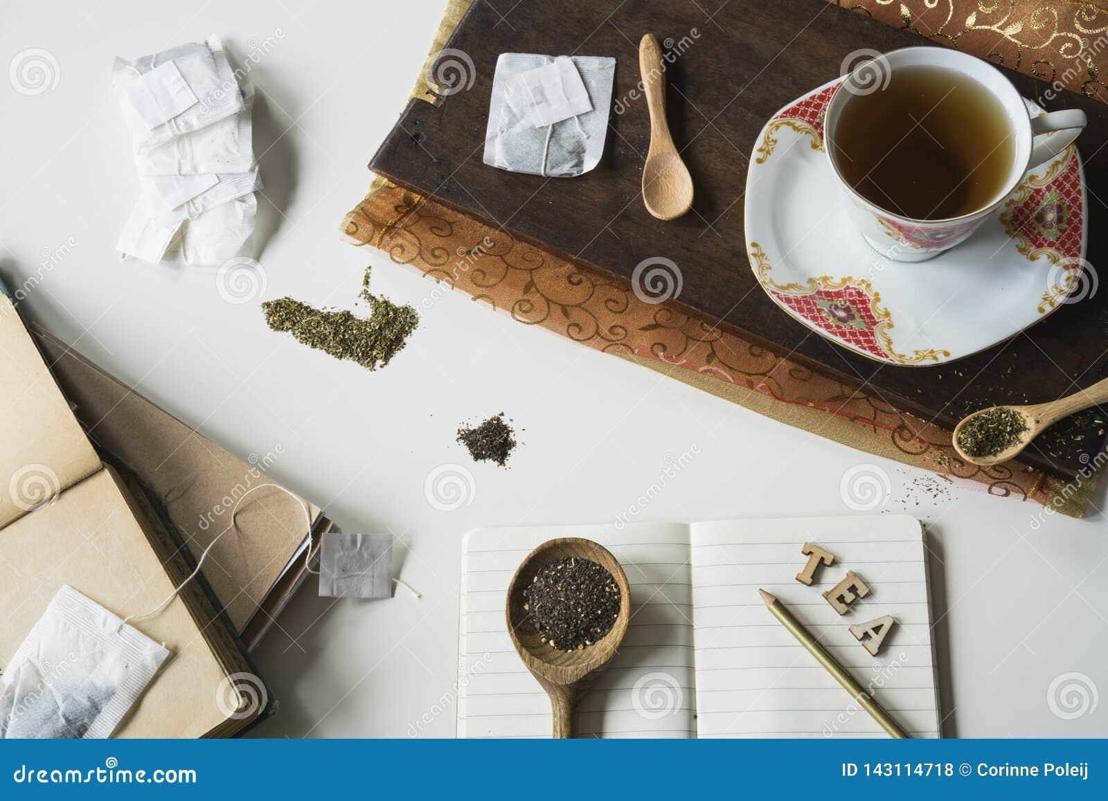 Cena do chá do vintage com copo e pires, placa de corte, colheres e livro do memorando