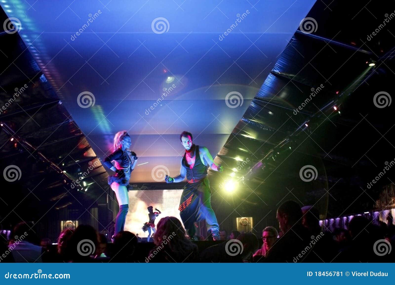 Cena do clube nocturno com mostra dos dançarinos e das luzes