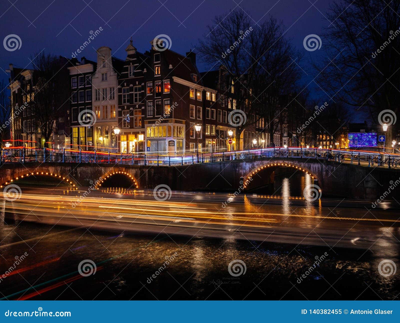 A cena típica do canal de Amsterdão com casas tradicionais e as fugas claras formam barcos na noite