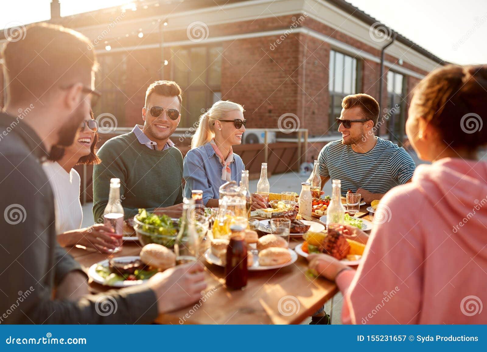 Cenare degli amici o partito del bbq sul tetto