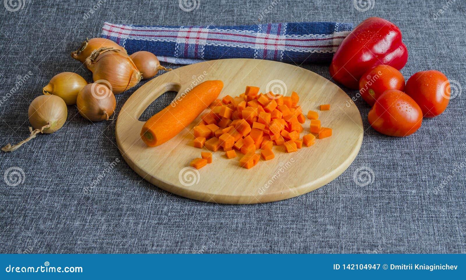 Cenouras cortadas em uma placa de corte de madeira Cebolas, tomates, pimenta de sino Toalha de cozinha Em uma fundo-imagem cinzen