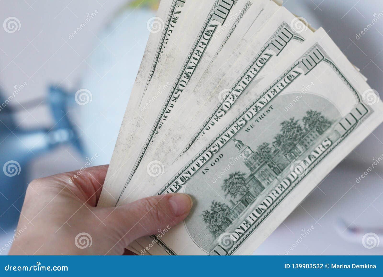 Cent billets d un dollar à disposition La main femelle tient beaucoup de dollars