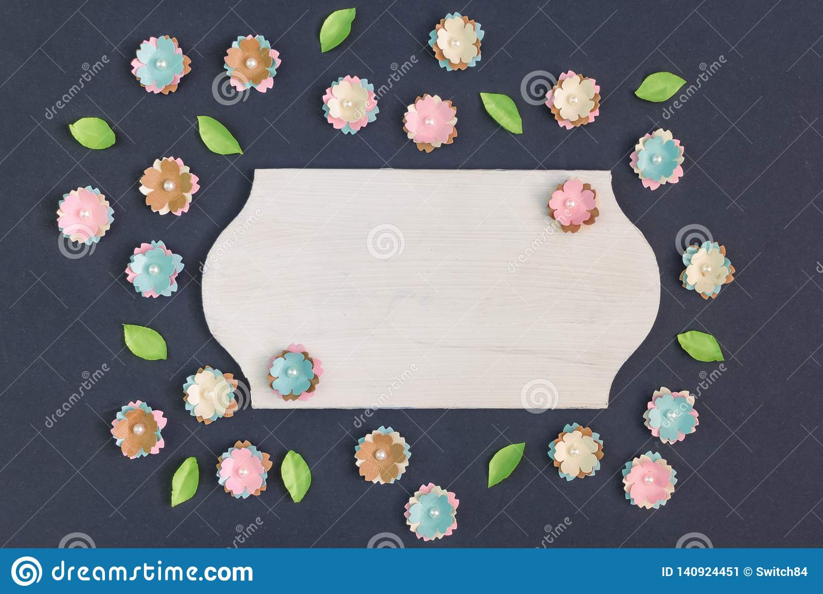 In the center of the black background is an empty plate. Around chaotically lie small artificial paper flowers.