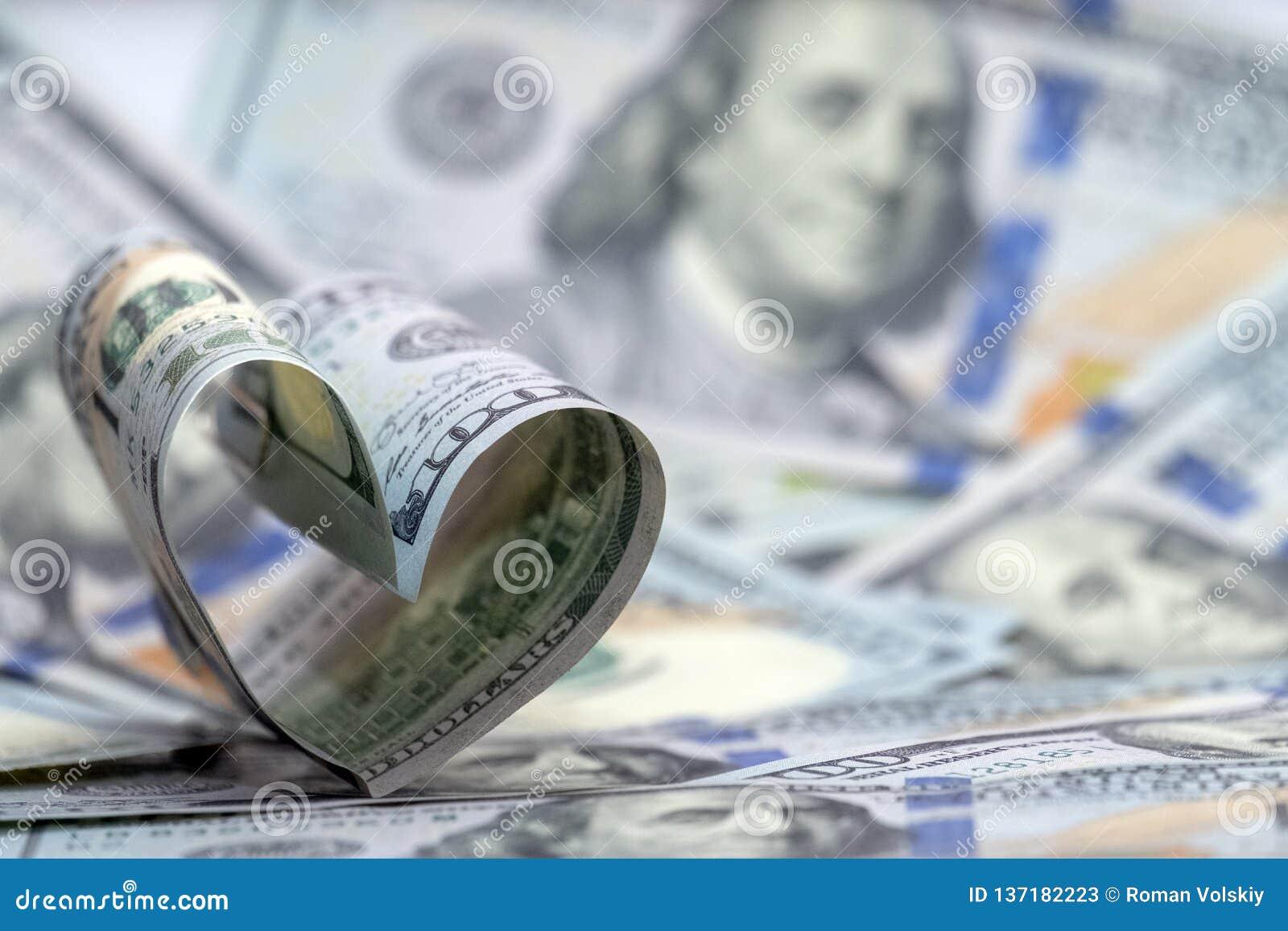 Cento banconote del dollaro degli S.U.A. sotto forma di un cuore Cenni storici dei soldi Amore finanziario di concetto e un regal