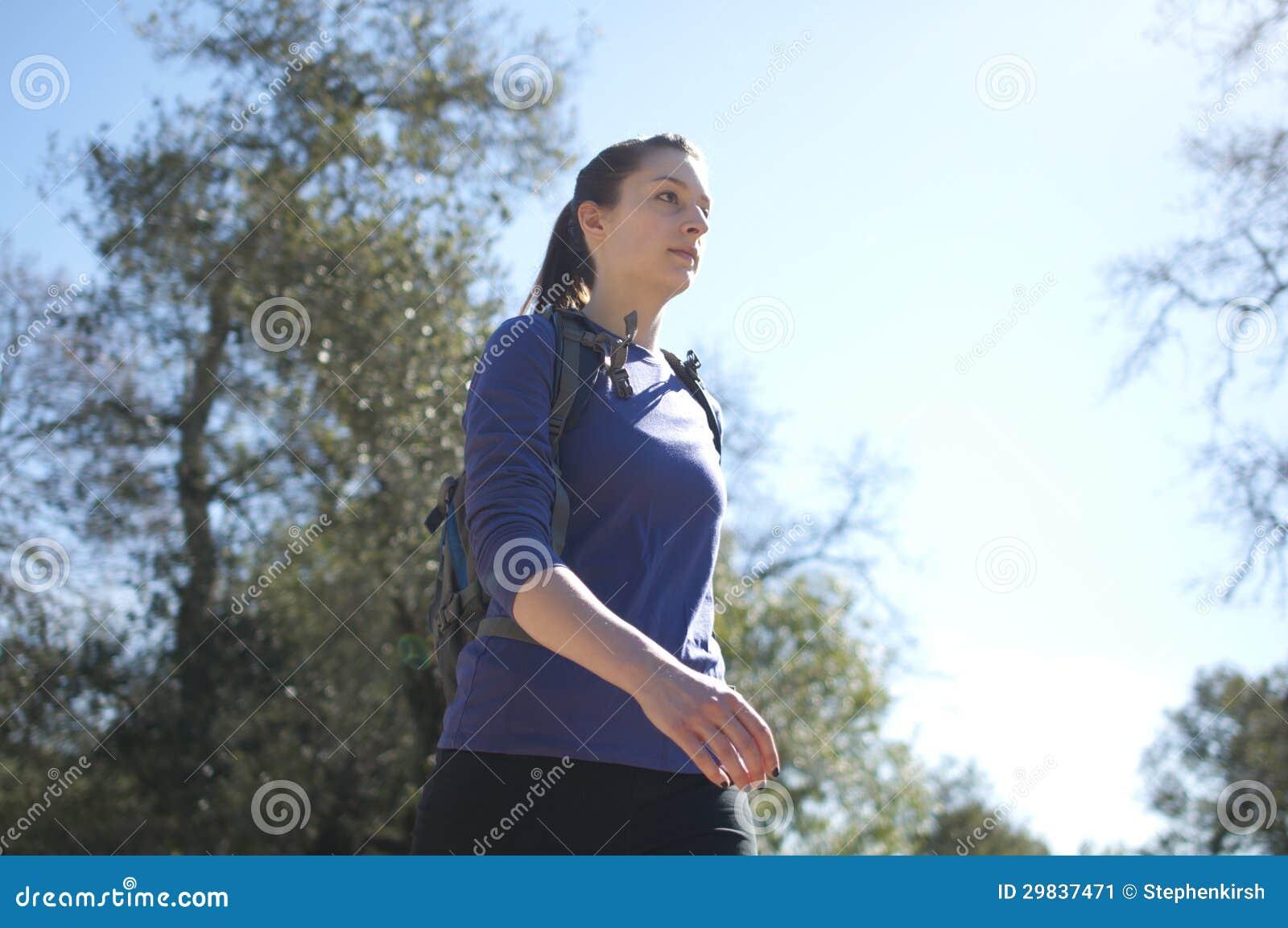 Centrado perto acima da mulher que caminha na camisa azul que enfrenta certo
