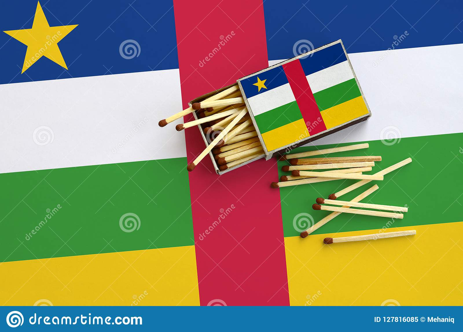 Central African Republic flag is shown on an open matchbox, from which several matches fall and lies on a large flag