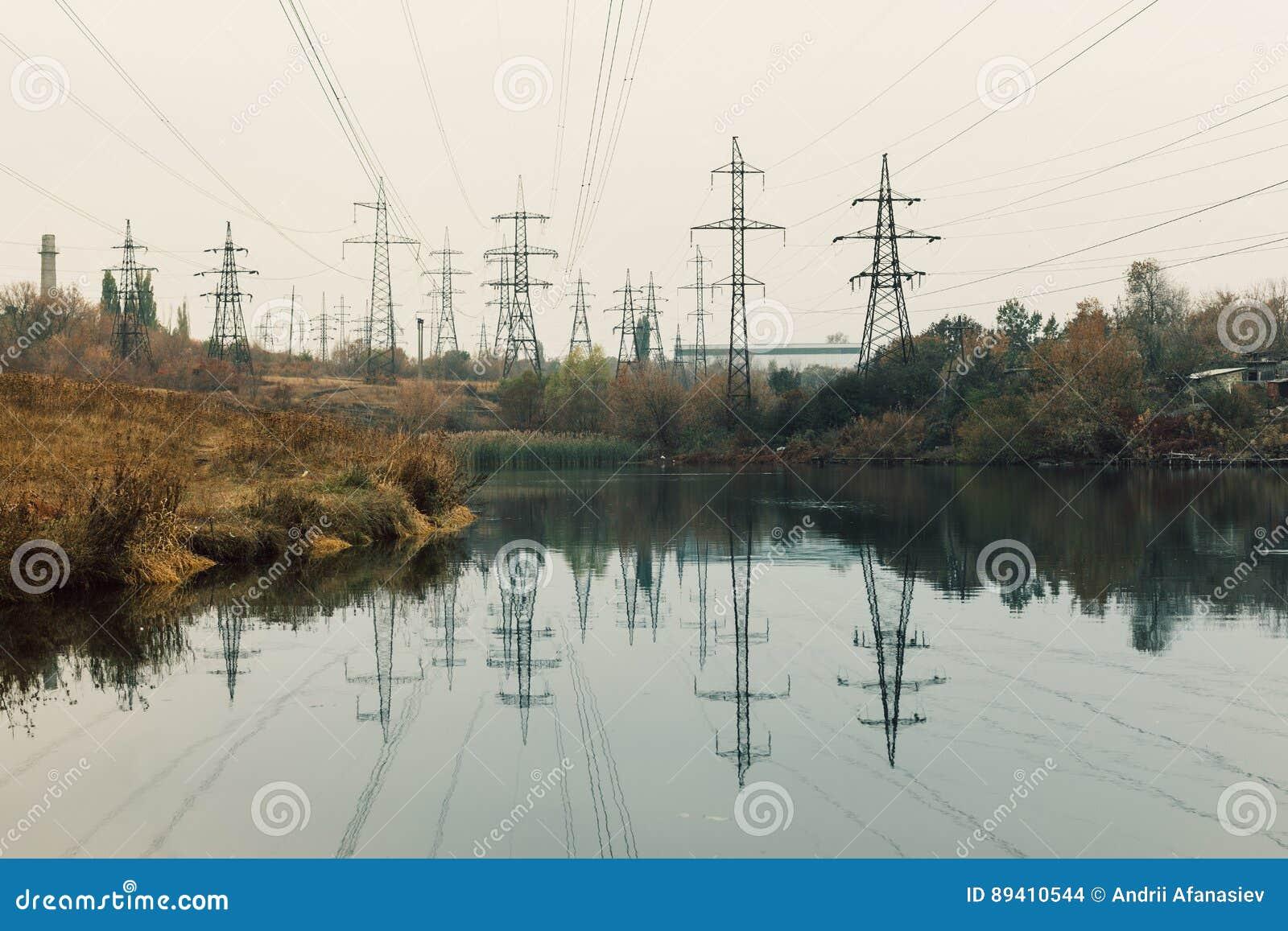 Central elétrica de carvão na área bonita completa das árvores e do lago, reflexão de espelho do polo energético e central elétri