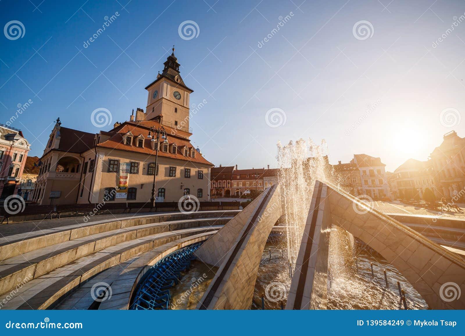 Central fyrkant för stad (Piata Sfatului) med kommunfullmäktigekorridortornet, sikt för springbrunnmorgonsoluppgång, läge Brasov,