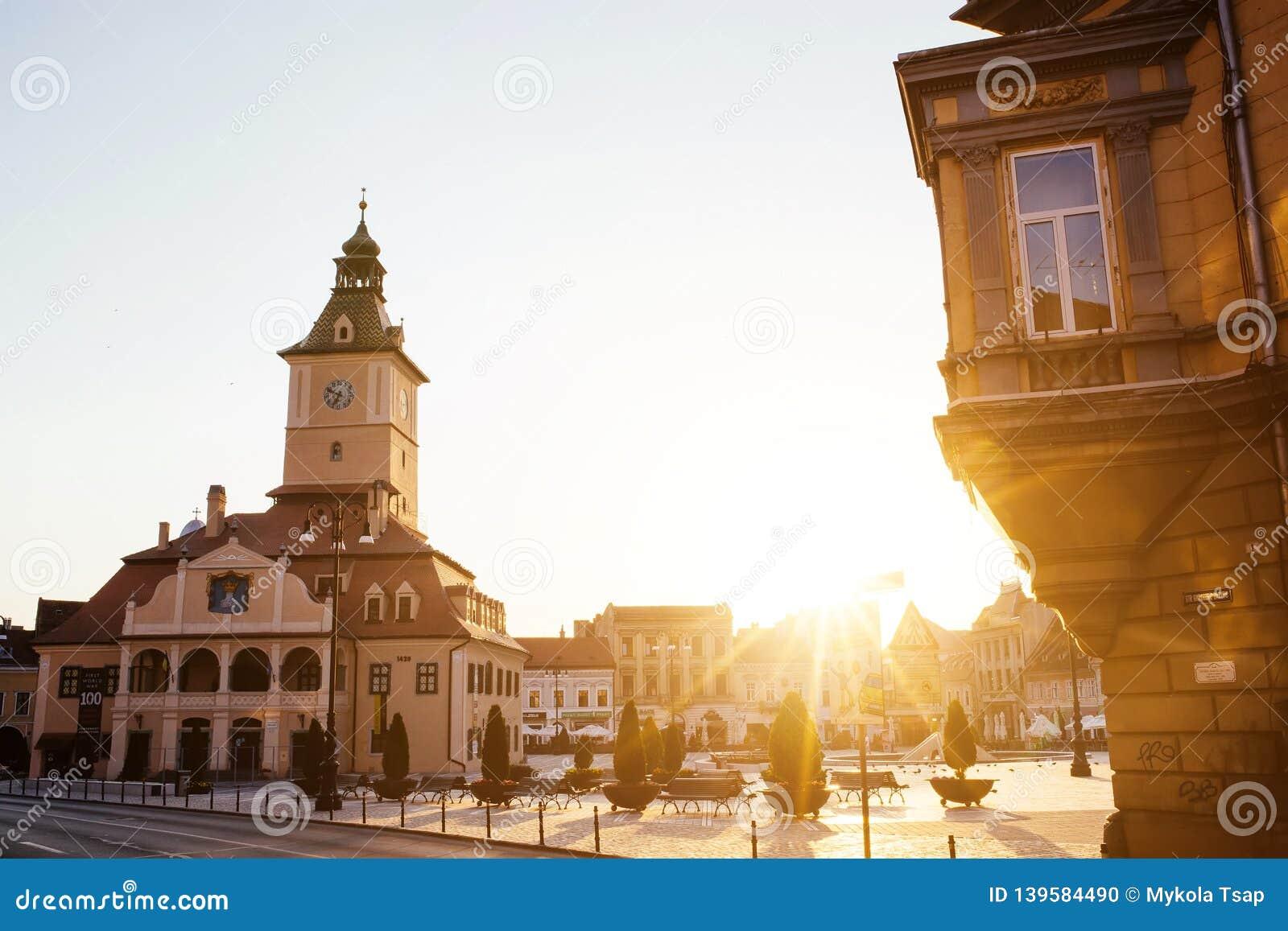 Central gata för stad med sikten för soluppgång för morgon för kommunfullmäktigekorridortorn, läge Brasov, Transylvania, Rumänien