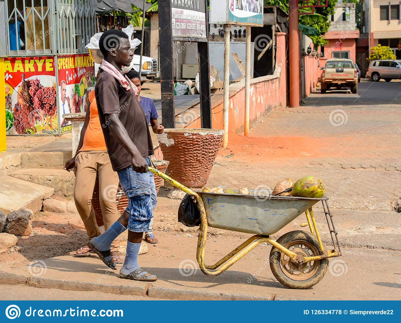 Unidentified Ghanaian man pulls a cart with coconuts in local v