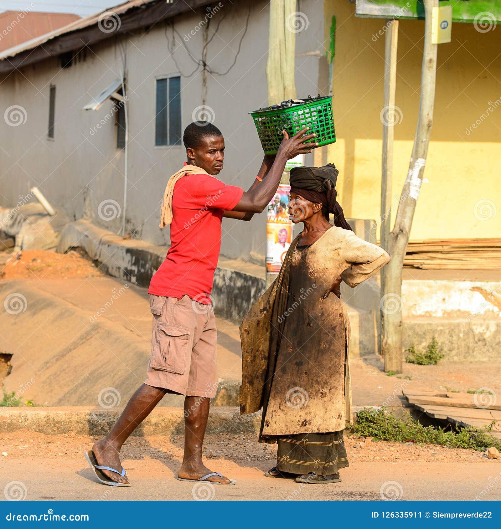 Unidentified Ghanaian man puts a basket on woman s head in loca