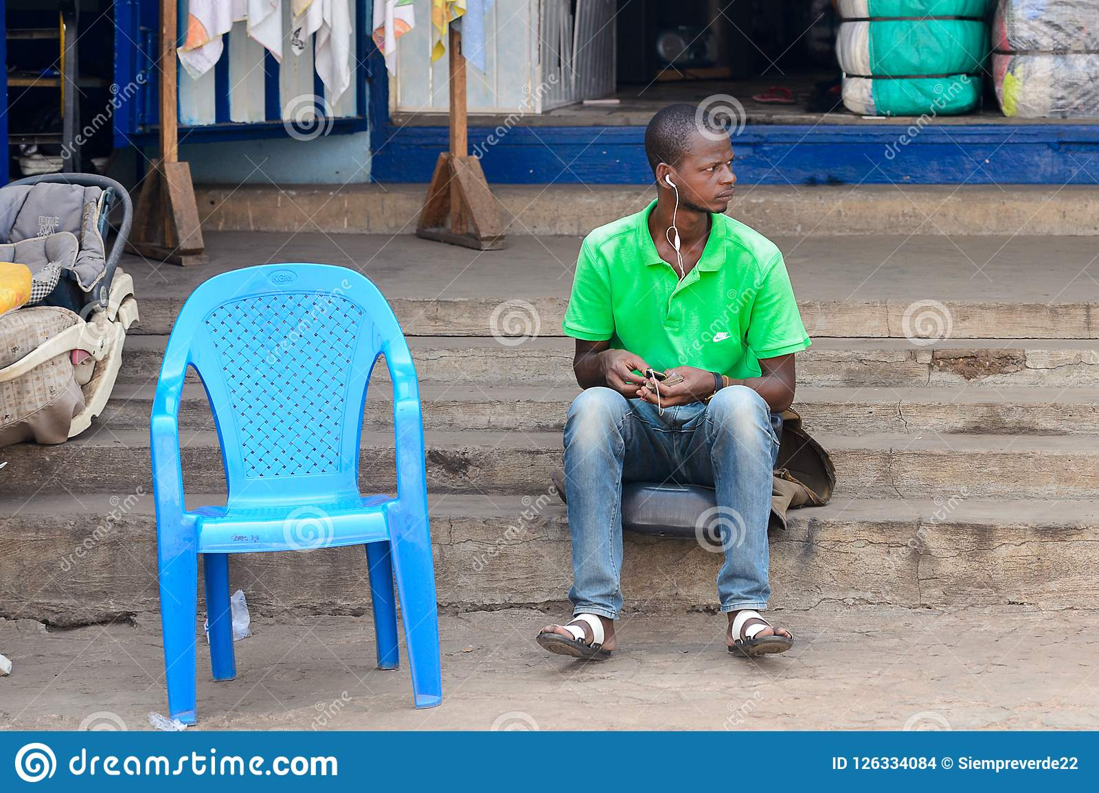 Unidentified Ghanaian man sits on stairs and listens to music i