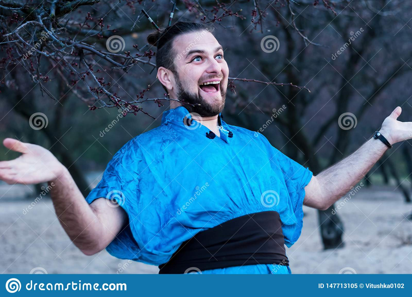 Centre sélectif d homme barbu riant enthousiaste dans la position bleue de kimono avec les bras tendus regardant l awa