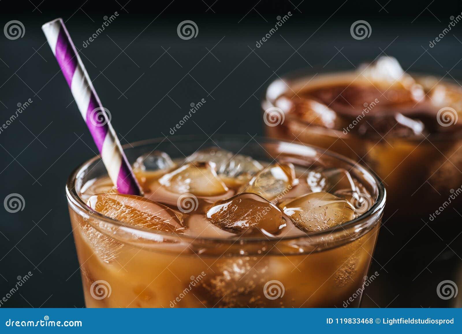 Centre sélectif de verre de café glacé froid avec la paille sur le fond foncé
