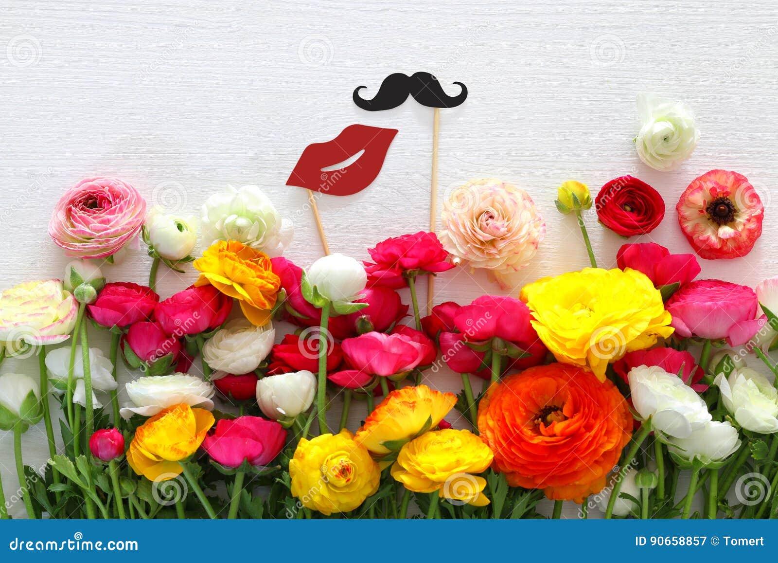 Centro de flores, labios falsos de papel y bigote en palillos