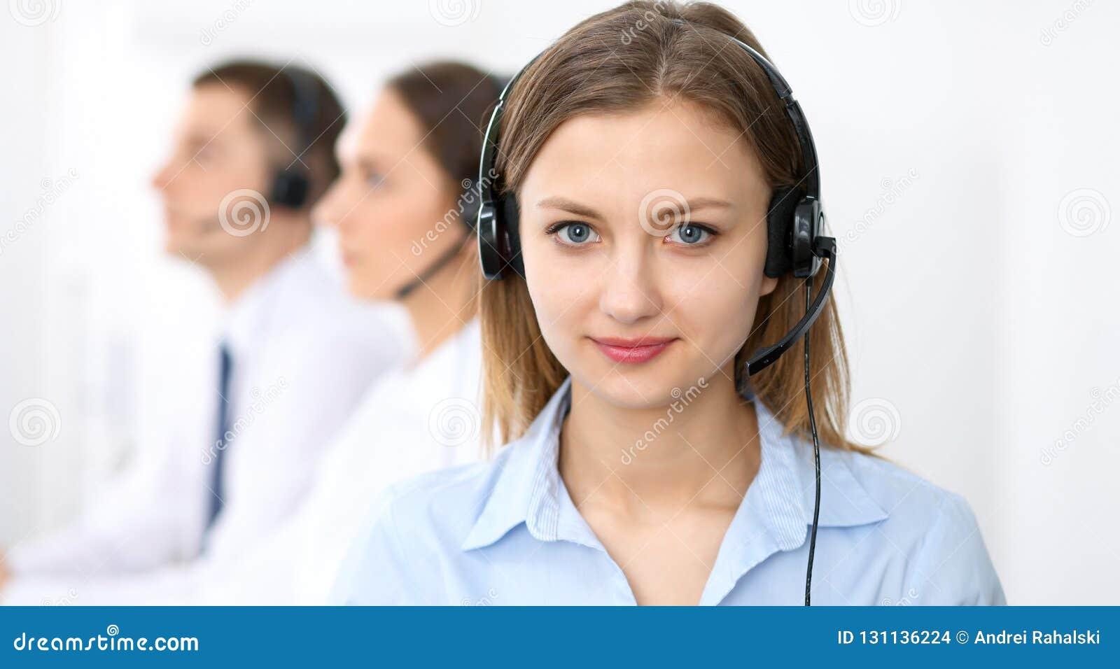 Centrum telefoniczne operatorzy Skupia się na młodej rozochoconej uśmiechniętej kobiecie w słuchawki Biznesu i obsługi klienta po