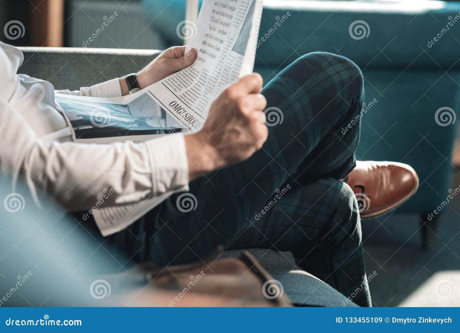 CEO (главный исполнительный директор) нося приданные квадратную форму брюки и кожаные ботинки читая газету