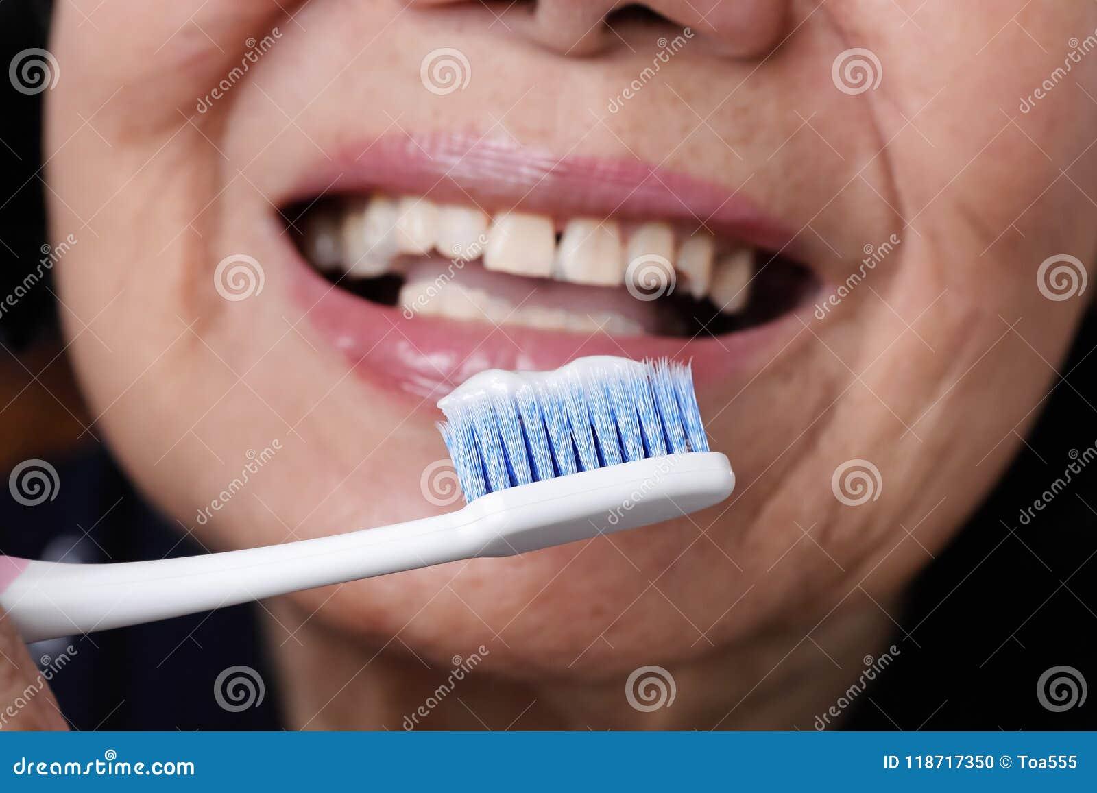 Cepillo de dientes del uso de la mujer que intenta mayor asiática, temblor de la mano