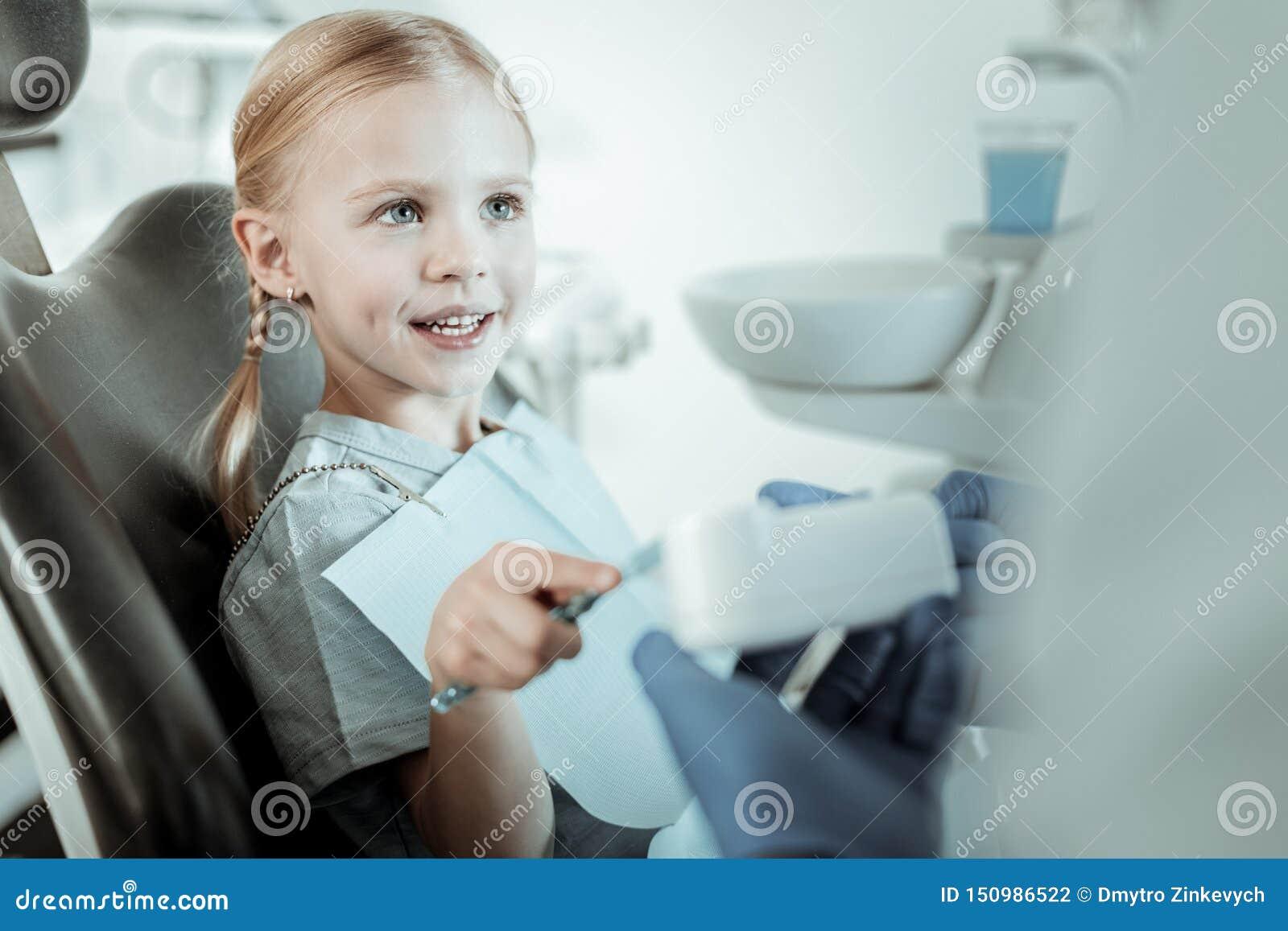 Cepillo de los dientes de la muchacha que lleva interesada bonita mientras que se sienta
