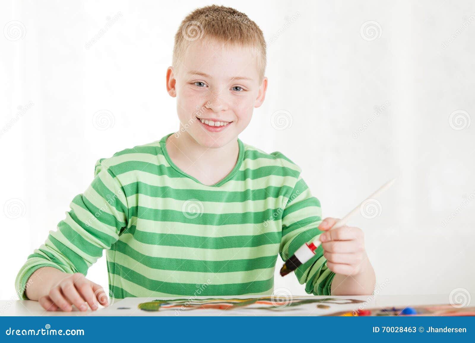 Cepillo sonriente asentado de los controles del muchacho a disposición