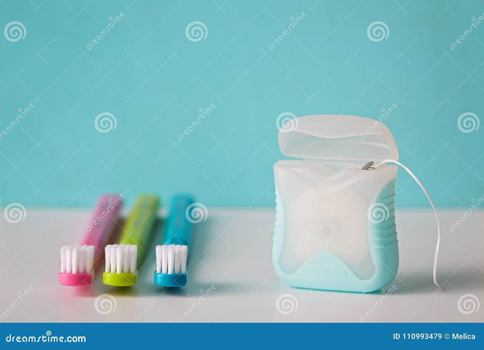 Cepillos de dientes coloridos y seda dental
