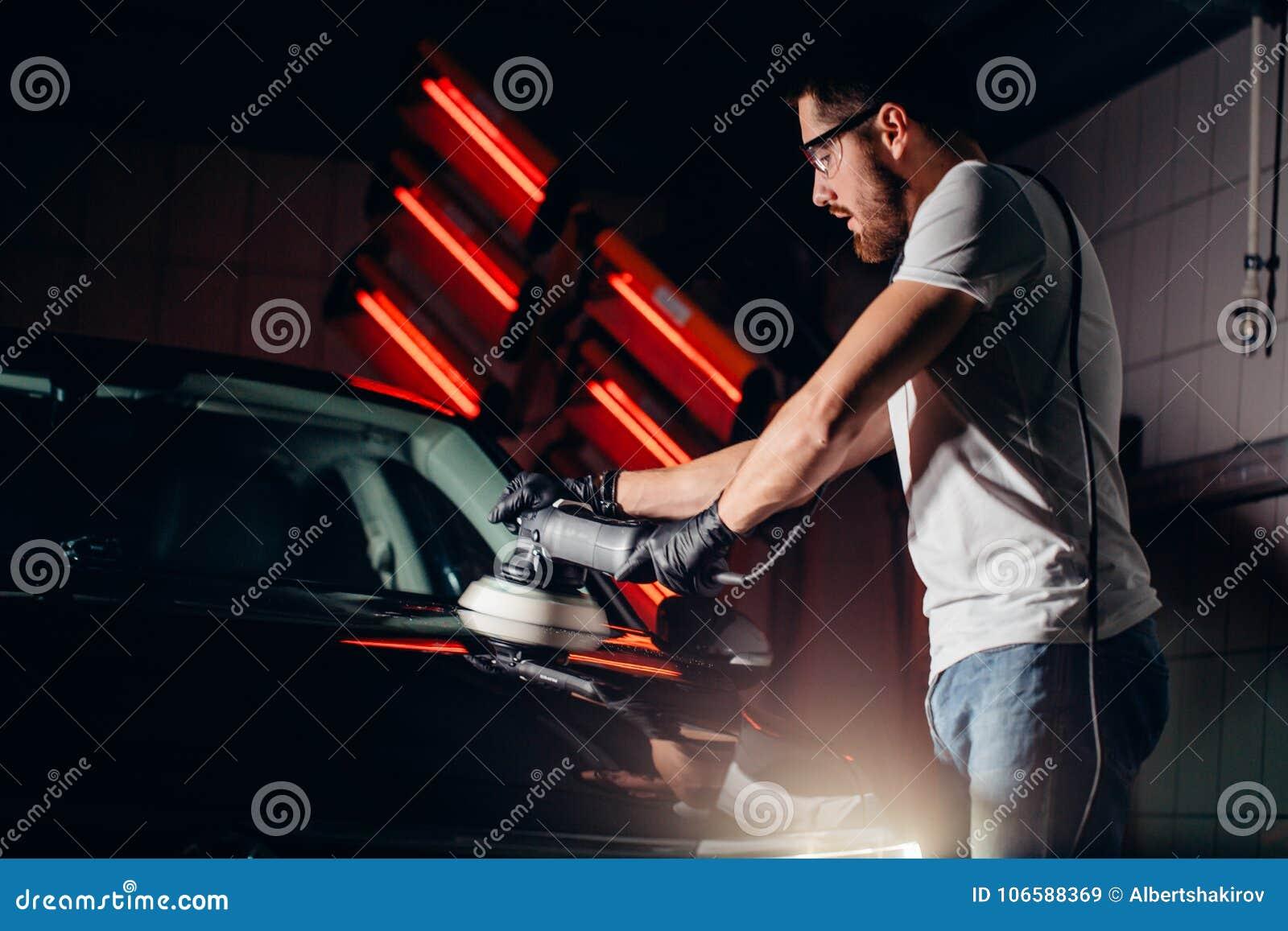 Cera del pulimento del coche manos del trabajador que sostienen un pulidor
