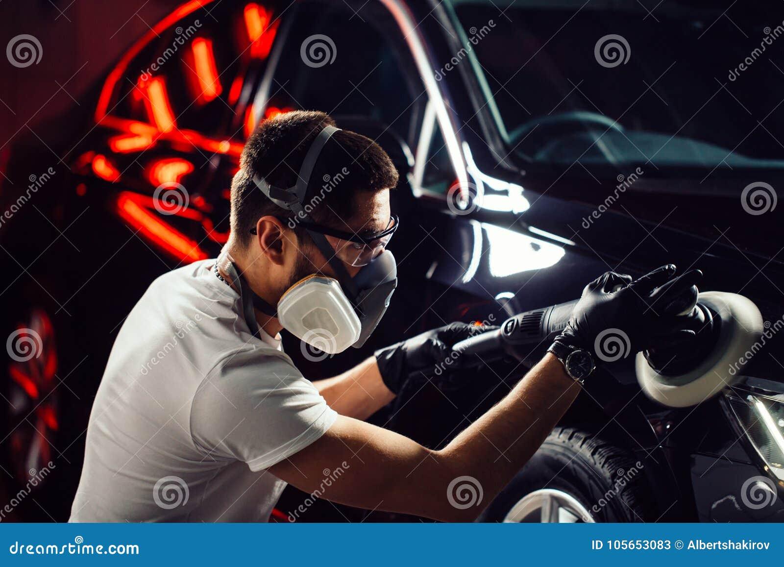 Cera do polimento do carro mãos do trabalhador que guardam um polisher