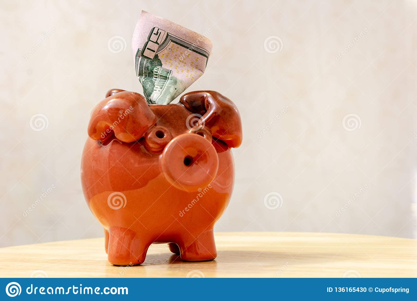 Ceramic brown piggy bank with 50 US dollar bill on a light background