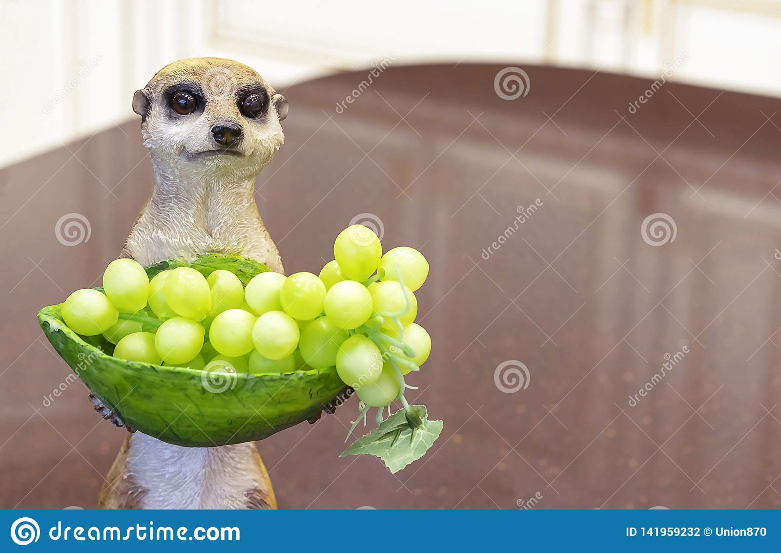 Ceramic figurine of a meerkat with a vase of grapes
