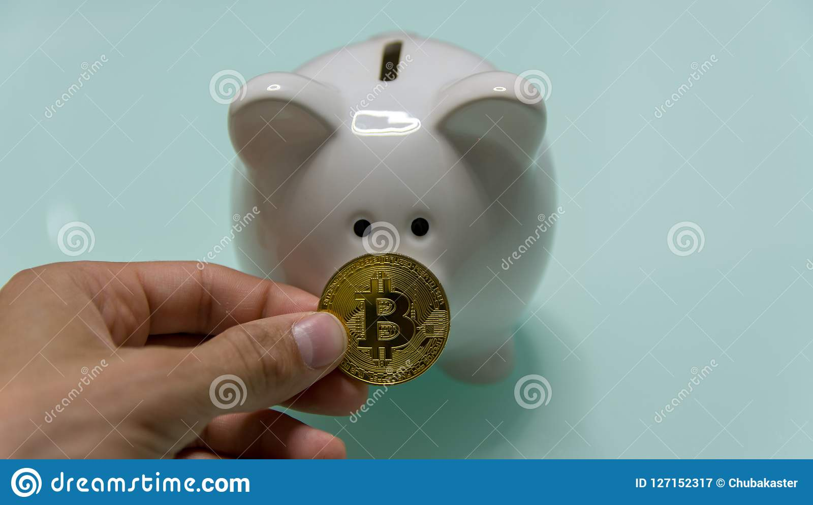 Ceramic Piggy bank with bitcoin in bam hand on front of image closeup