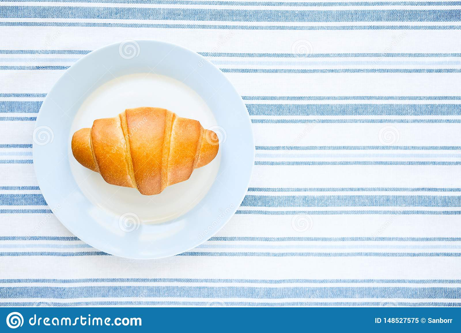 Ceramic plate with freshly baked bakery, croissant on a striped linen towel. The concept of organic, farm food. The view from the
