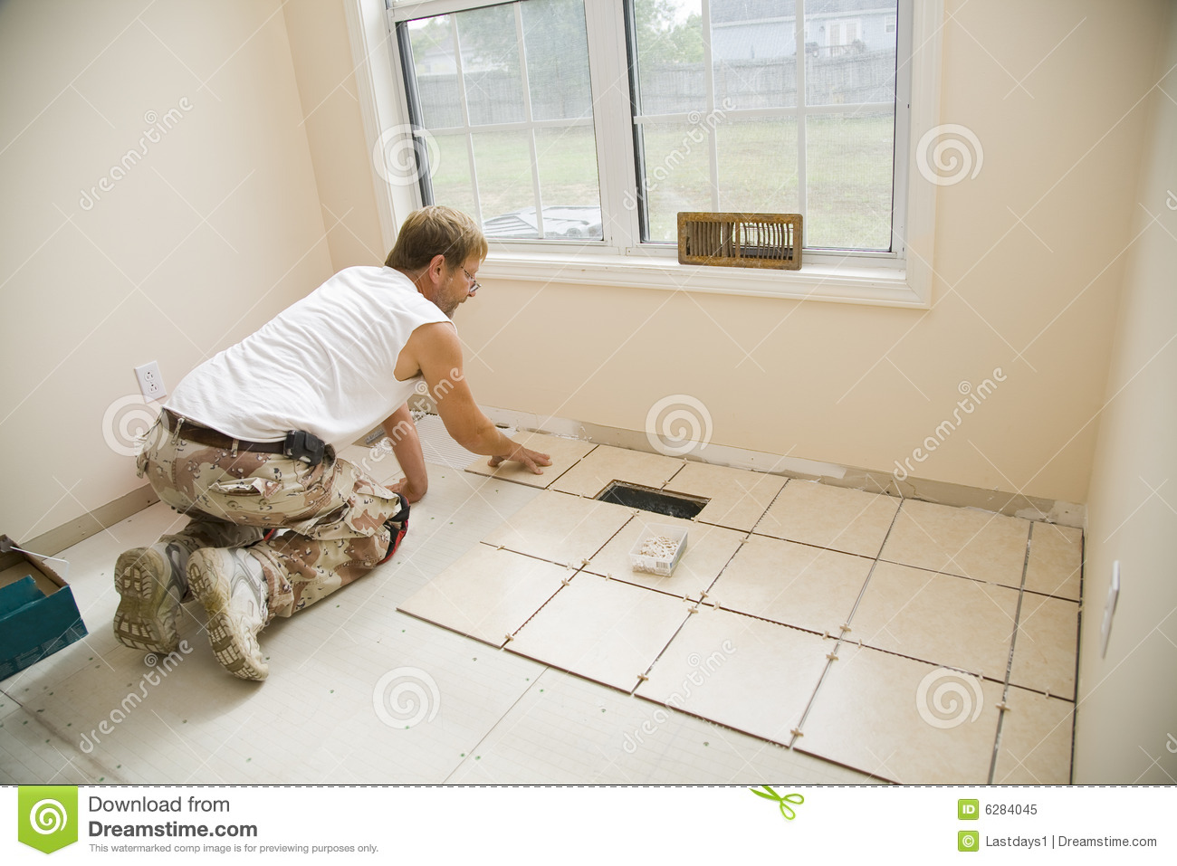 Ceramic tile installer stock image image of kneeling 6284045 man installing ceramic tile in customers kitchen getting ready to sell home dailygadgetfo Gallery