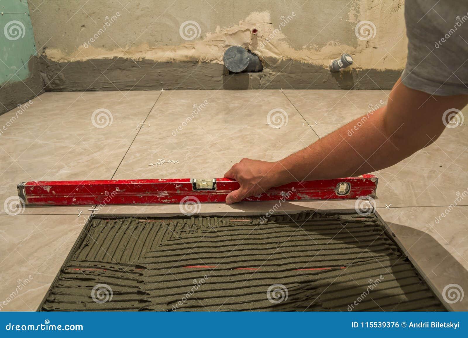 Ceramic Tiles And Tools For Tiler Worker Hand Installing Floor