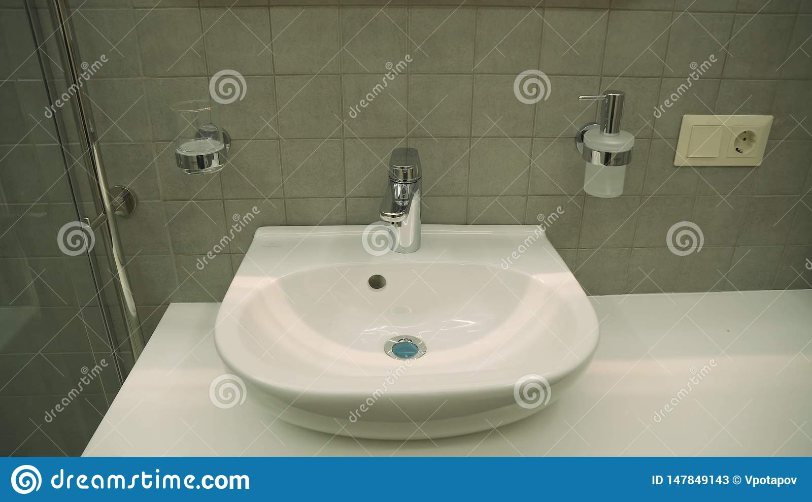 Ceramic washbasin with hot and cold faucet in luxury hotel bathroom.