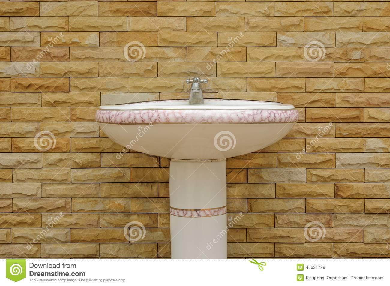 Ceramic White Washbasin With A Faucet On Brick Background Stock
