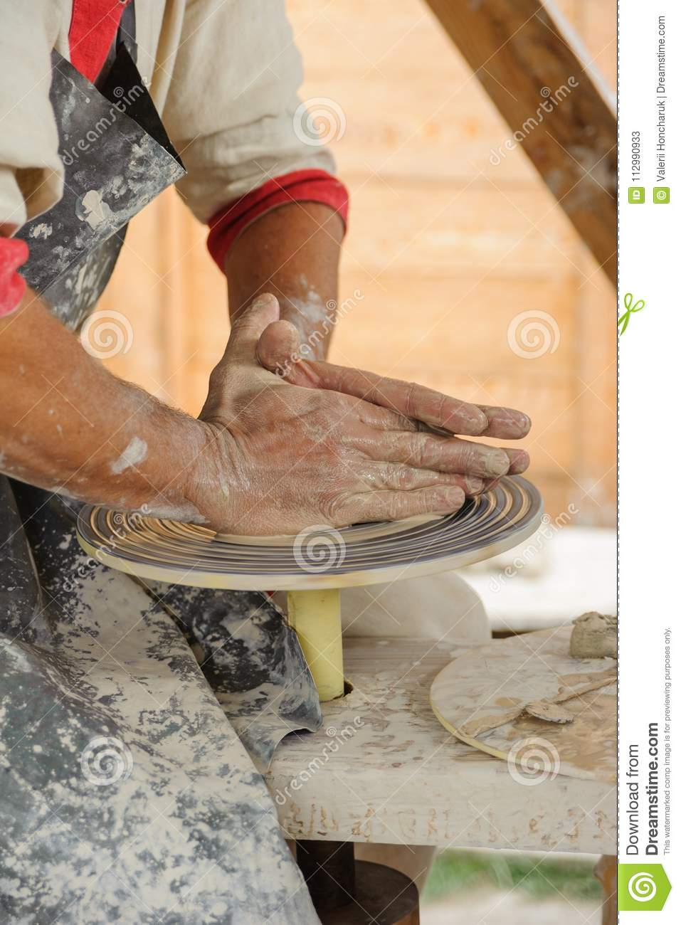 Ceramics - hands of the master makes a clay pitcher on the Potter wheel, side view